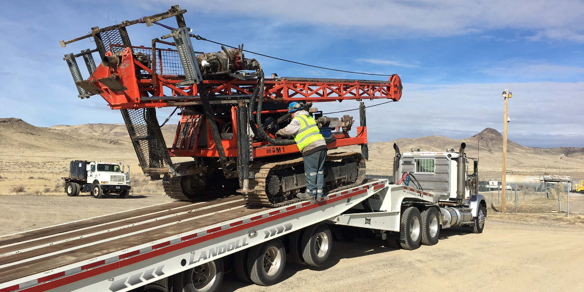 Loading well driller onto lo-bed truck